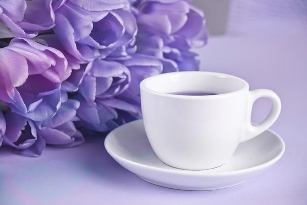Una tazza di tè e tulipani viola sul tavolo
