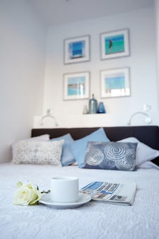 Una tazza di tè e una rosa bianca si trovano sul letto in un ambiente luminoso