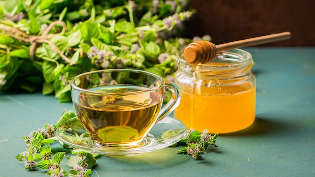 Una tazza di tè fresco con le foglie di menta della melissa su legno