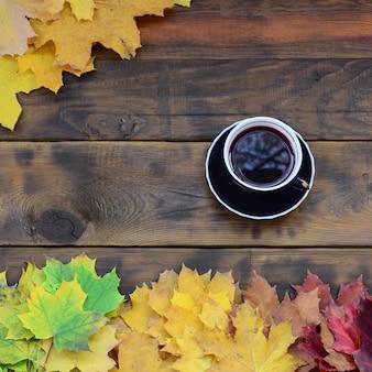 Una tazza di tè in un insieme di ingiallimento foglie cadute d'autunno su uno sfondo