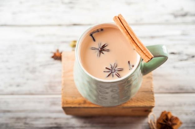 Una tazza di tè masala. spezie, chiodi di garofano, finocchio, cannella, cardamomo, latte.