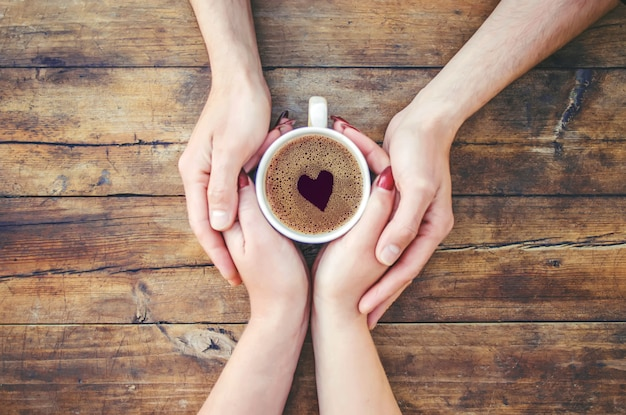 Una tazza di tè nelle mani. messa a fuoco selettiva bere.