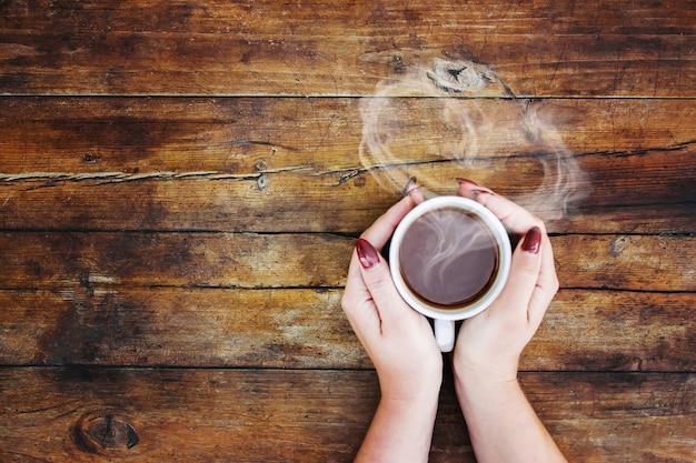 Una tazza di tè nelle mani. messa a fuoco selettiva