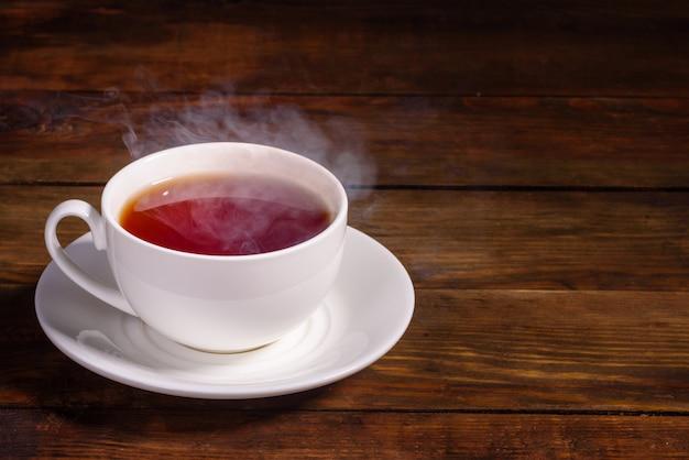 Una tazza di tè nero appena preparato, vapore che fuoriesce, luce calda e morbida