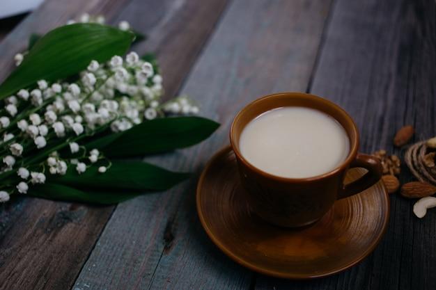 Una tazza di tè, noci, bouquet di gigli su un fondo di legno