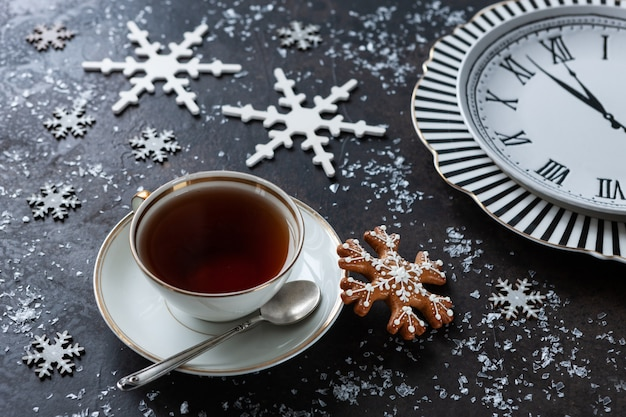 Una tazza di tè, pan di zenzero e un orologio con le frecce. sfondo di natale