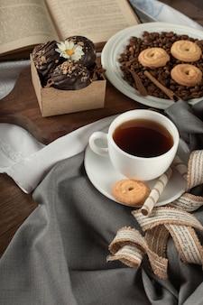 Una tazza di tè, praline e biscotti