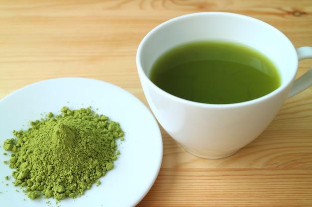 Una tazza di tè verde matcha caldo con un piccolo piatto di polvere di tè matcha
