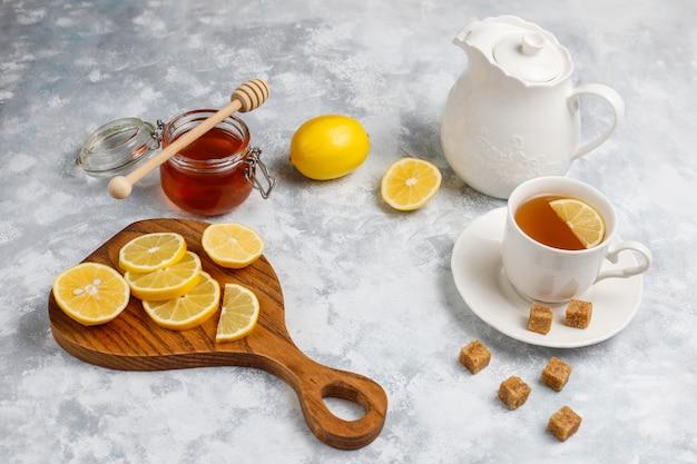 Una tazza di tè, zucchero di canna, miele e limone su cemento. vista dall'alto, copia spazio