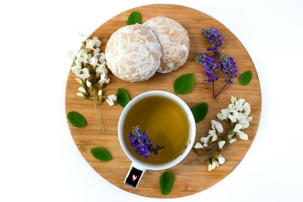 Una tazza di tisana e biscotti al miele ricoperti di glassa di zucchero bianco su una tavola di sabbia di legno. fiori di acacia bianca e fiori di campo.