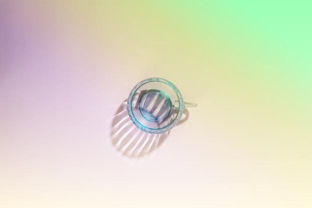 Una tazza di vetro blu con lunghe ombre riflettenti su uno sfondo colorato,