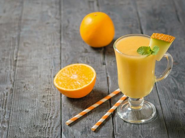 Una tazza di vetro con frullato di melone e arancio su un tavolo di legno nero.