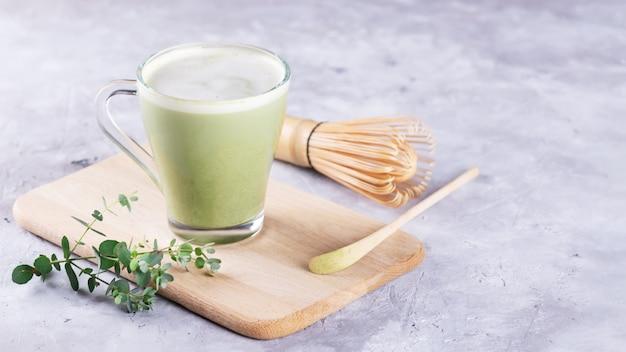 Una tazza di vetro di latte fresco matcha, tè verde al latte