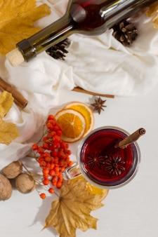 Una tazza di vin brulè con spezie, bottiglia, sciarpa, spezie, foglie secche e arance sul tavolo. mood autunnale, metodo per scaldarsi al freddo, copyspace.
