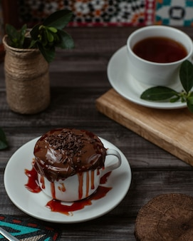 Una tazza dolce di gustosa mousse al cioccolato con sciroppo di fragole all'interno servita con una tazza di tè