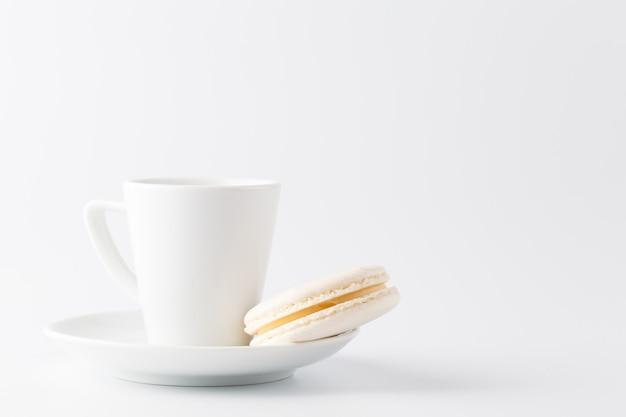 Una tazzina di caffè espresso con macaron bianco