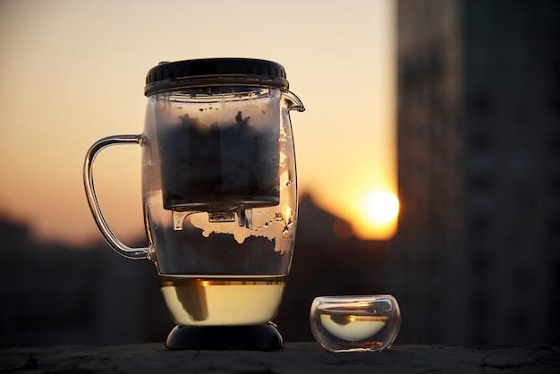 Una teiera di vetro e una tazza di tè su uno sfondo sfocato della città di sera alla luce del tramonto.