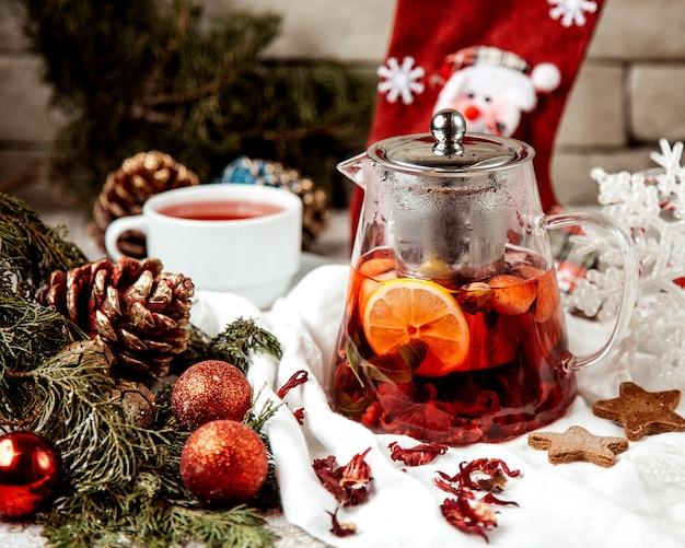 Una teiera di vetro riempita con tè al lampone e fragola con limone e menta