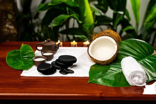 Una teiera e una tazza di argilla posizionate di fronte a un asciugamano di spugna su cui sono pietre per pietre terapeutiche, un asciugamano attorcigliato, una noce di cocco rotta e foglie di piante