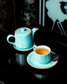Una teiera e una tazza di tè con biscotto laterale