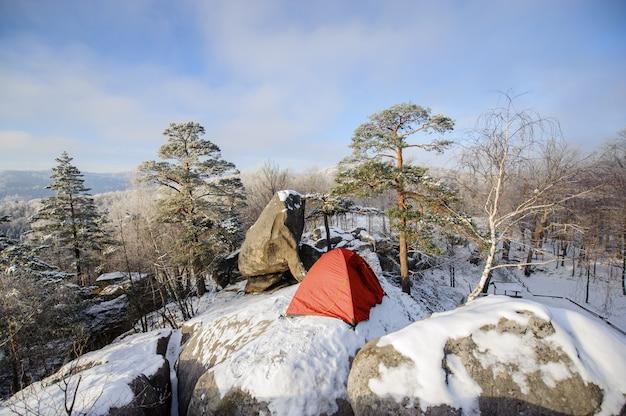 Una tenda rossa nella neve in piedi sulla cima della montagna rocciosa al mattino durante un'avventura estrema.