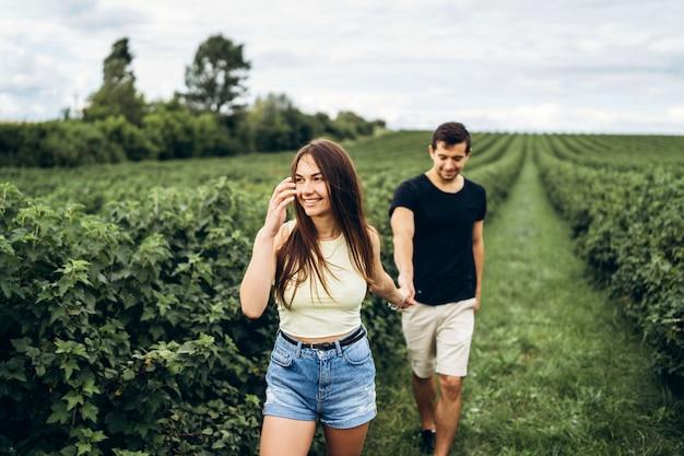 Una tenera coppia amorosa che cammina in un campo di ribes. una donna sorridente con i capelli lunghi conduce un uomo, tenendogli la mano