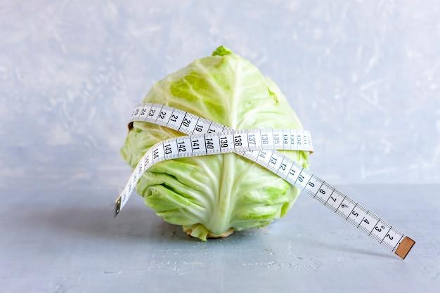 Una testa di cavolo fresco e un centimetro in vita. concetto di digiuno intermittente, dieta chetogenica, perdita di peso