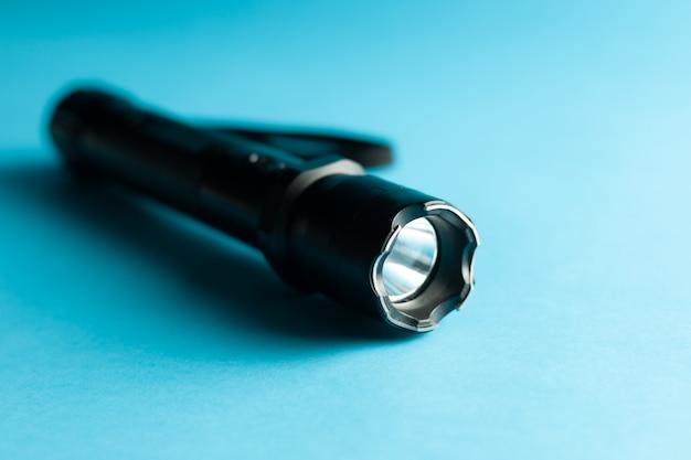 Una torcia elettrica di metallo nero con shock su sfondo blu