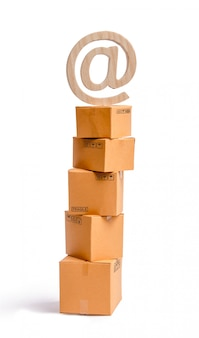 Una torre di scatole di cartone e un simbolo e-mail in cima.