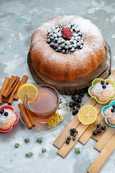 Una torta alla frutta con vista dall'alto, deliziosa e rotonda, formata con blu fresco, bacche e insieme a una tazza di tè su una torta luminosa