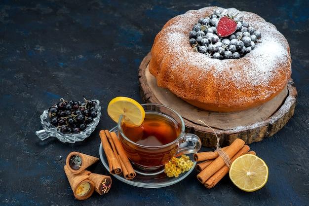 Una torta alla frutta vista frontale deliziosa e rotonda formata con blu fresco, frutti di bosco e insieme a una tazza di tè su fondente, zucchero dolce torta biscotto