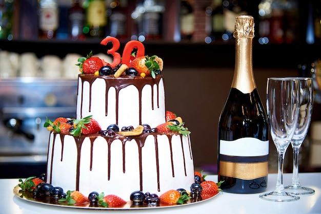 Una torta bianca a due livelli con frutta fresca e cioccolato si trova accanto a una bottiglia di champagne