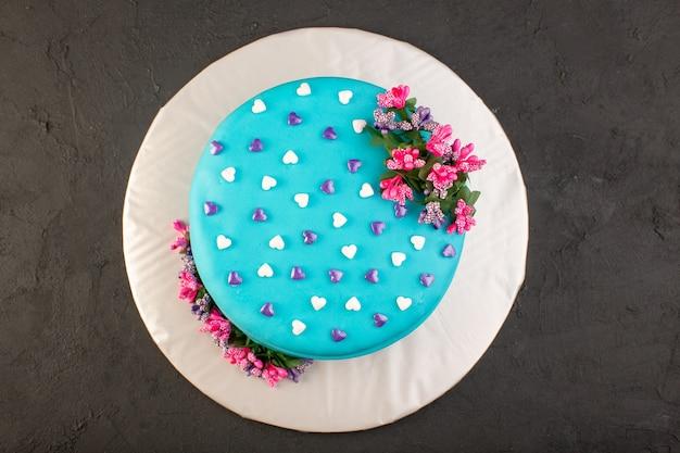 Una torta di compleanno blu con vista dall'alto con fiore in cima