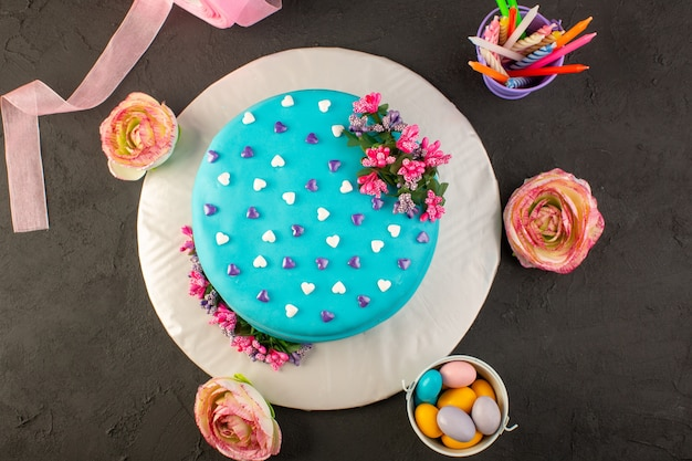 Una torta di compleanno blu con vista dall'alto con fiori e caramelle tutt'intorno