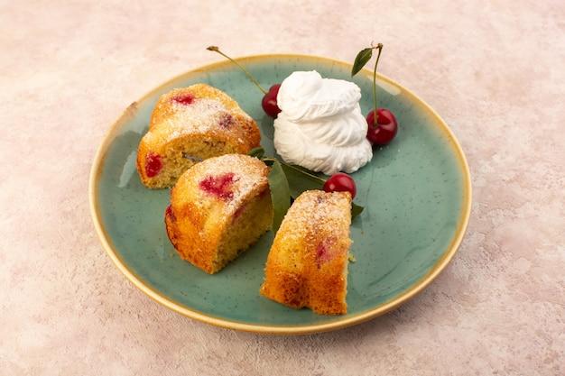 Una torta di frutta al forno vista frontale deliziosa affettata con ciliegie rosse all'interno e zucchero in polvere all'interno del piatto verde rotondo sul rosa