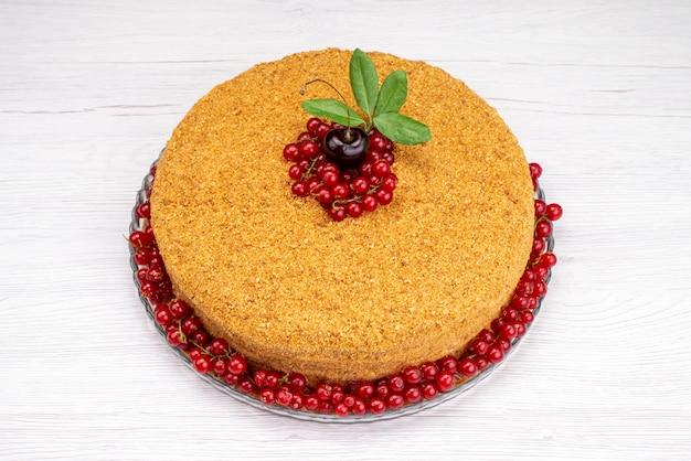 Una torta di miele rotonda di vista superiore deliziosa e al forno con i mirtilli rossi sulla foto dello zucchero del biscotto della torta leggera dello scrittorio