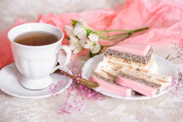 Una torta dolce della tazza della rosa di rosa con la teiera e la tazza sul tavolo