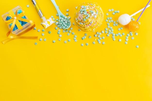 Una torta gialla con vista dall'alto insieme a caramelle a forma di stella verde su colore giallo
