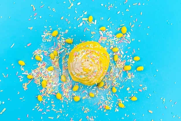Una torta gialla di vista superiore con le caramelle sul blu