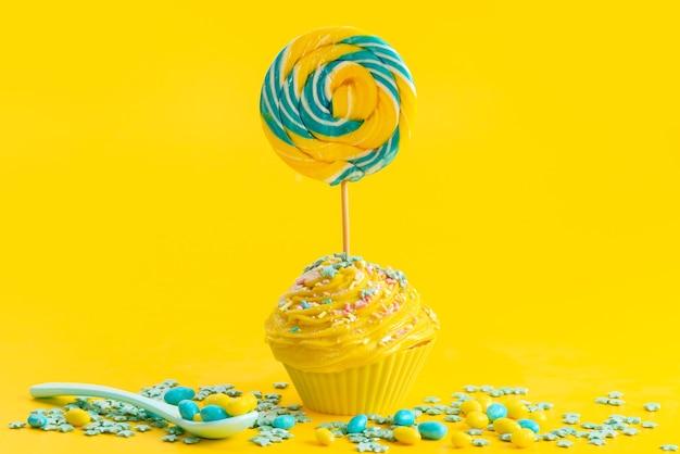 Una torta gialla vista frontale con lecca-lecca in cima insieme a caramelle colorate su giallo