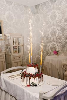 Una torta nuziale a due livelli bianca con anni di lamponi e more e una fontana di fuochi d'artificio nella torta