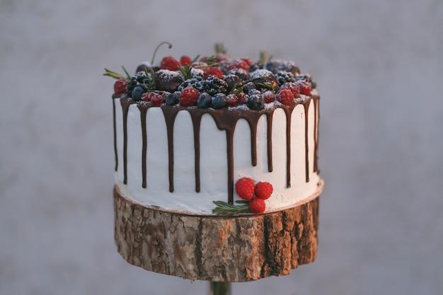 Una torta nuziale con frutti di bosco, versata con cioccolato su una mensola in legno.