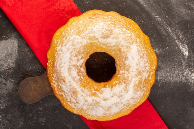 Una torta rotonda al forno vista dall'alto con zucchero in polvere sulla scrivania in legno