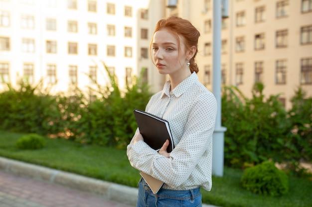 Una triste ragazza dai capelli rossi con le lentiggini sul viso tiene una cartella tra le mani.