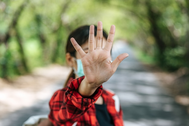 Una turista che porta uno zaino e solleva le cinque dita per vietare la strada.