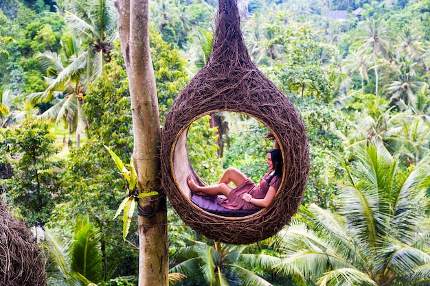 Una turista femmina è seduta su un grande nido di uccelli su un albero nell'isola di bali
