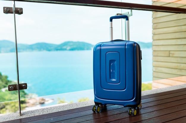 Una valigia da viaggio blu in piedi su un balcone aperto con vista sul mare e sulla natura. vacanze e viaggi