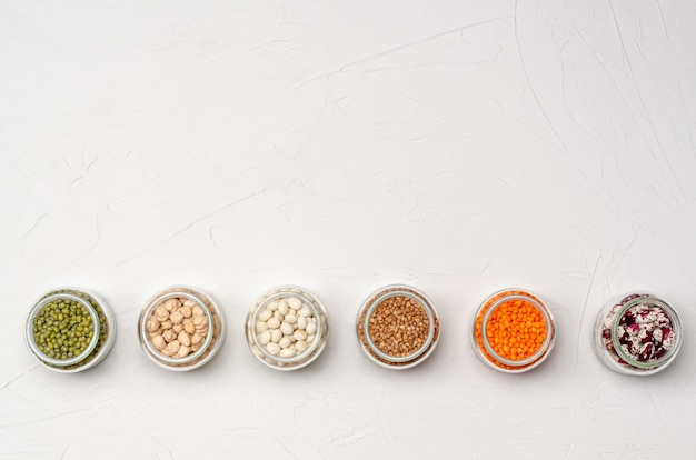 Una varietà di cereali secchi per vegetariani in barattoli di vetro: lenticchie, ceci, fagioli, grano saraceno su una superficie bianca