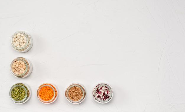 Una varietà di cereali secchi per vegetariani in barattoli di vetro: lenticchie, ceci, fagioli, grano saraceno