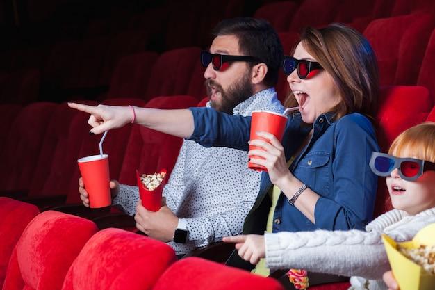 Una varietà di emozioni umane di amici che tengono una cola e popcorn al cinema.